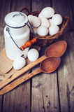 Country kitchen Still Life. Enamel milk can, eggs in a wicker basket and wooden spoons on a background of the old board, vintage style Royalty Free Stock Photography