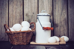 Country kitchen Still Life. Enamel milk can, eggs in a wicker basket and wooden spoons on a background of the old board, vintage style Stock Photos