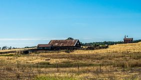 Rural life in California. Old ranch among the fields. Country landscape in California. A village house and an old-fashioned cattle farm among fields and hills stock images