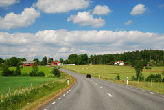 Country landscape with a road and farms. Asphalt bent road is running between green fields and farms. Country highway is photographed with diminishing Stock Photos