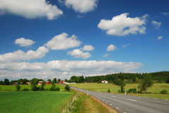 Country landscape with road, farms and clouds. Asphalt bent road is running between green fields and farms. Country highway is photographed with diminishing Royalty Free Stock Photography