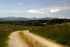 Country Lane. A dirt road in a field with mountains in the background Royalty Free Stock Photo