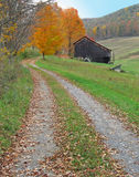 Country lane in autumn. Leading past a rustic barn Royalty Free Stock Photography