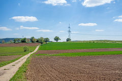 Country lane through farmland. Ploughed field, trees aside Royalty Free Stock Photography