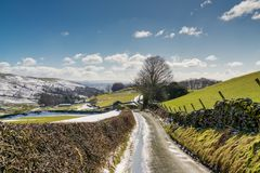 A country lane leading through snow spattered farmland. Stock Image