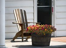 Country living. Adirondack chair and flowers on porch royalty free stock photo
