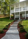 Country Living with Security Lit Steps. Country home has lit walkway to back door.  Two level home with balcony and fan.  Landscaped yard with Azalea bushes Royalty Free Stock Image
