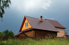 Country log house. A log bath house in the country against a stormy, cloudy sky royalty free stock photo