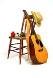 Country Love Song. A guitar rests against a wooden chair that is splattered with paint Stock Photos
