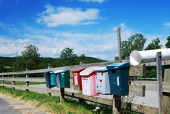 Country mailboxes on the fence. Various postboxes are hanging on the wood fence near the country road Royalty Free Stock Photo