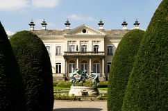 Country manor in summer. A country manor in summer. Three bronze statues are playing round the fountain Royalty Free Stock Image