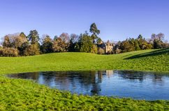 A country mansion and frozen pond. A country mansion set amongst trees with a frozen pond in the foreground Royalty Free Stock Photos