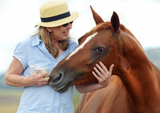 Country mature woman smiling relaxing fun with horse Stock Photo
