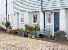 Country mews cottages. Photo of kent country mews cottages with cobbled path and pretty potted flowers and plants royalty free stock photography