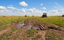 Country muddy roud and tractor Stock Images