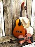 Country music background with stringed instruments. Guitar, banjo , violin and a cowboy hat leaning against a wood fence. Room for text or copy space Royalty Free Stock Photo