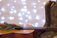 Country music christmas background with guitar and cowboy shoes. Country music christmas background with acoustic guitar and cowboy shoes royalty free stock image
