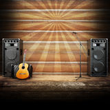 Country music stage or singing background. Microphone, guitar and speakers with wood flooring and sunburst background. Advertising concept with room for text Royalty Free Stock Photos