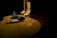 Country Music Symbols. Selective focus on the guitar in the foreground with cowboy boots in the background under the spotlight royalty free stock photos