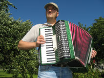 Country musician. Young man,  playing the accordion in the garden Royalty Free Stock Photo