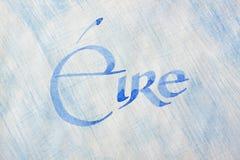 Country name. Ireland Eire. Handwritten country name over blue painted paper background. Ireland Eire. Latin gaelic celtic script. Irish language Stock Image