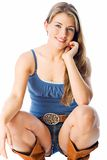 Country outfit. Natalie wears tight shorts with cowboy belt and boots Royalty Free Stock Photography