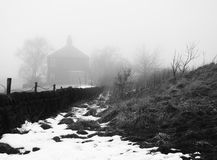 Country path in heavy fog with snow a wall trees and house Royalty Free Stock Photos