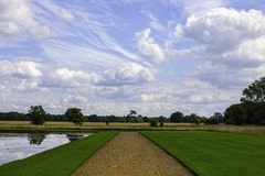 Country path with `oil painting` landscape. A country path in the English countryside with a painterly cloudy sky. Gravel path and formal lawns lead to the stock image