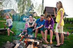 Country picnic. Scene - family having a barbecue over an open fire in the evening Stock Photo