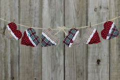 Country plaid Christmas hearts hanging on clothesline by rustic wooden background Royalty Free Stock Images