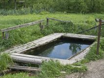 Country pond for washing and rinsing. With wooden boards floor Stock Photo