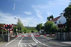 Country Railway Crossing. Red lights flash to tell the motorists that a train is coming and the red and white barriers go down to stop cars from crossing the Royalty Free Stock Photos