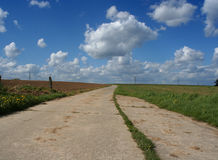 Country road. A quiet country road with impressive cloudy sky at the background royalty free stock image