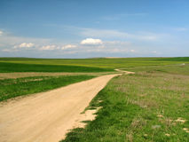 Country road. Between grass fields Stock Photo