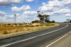 Country Road. In rural Australia with gumtrees and a water pumping windmill Royalty Free Stock Photography