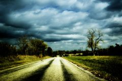Country Road. Old asphalt road in the country .. Uses edgy contrast and film grain to emphasize the old country mood Royalty Free Stock Photo