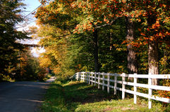 Country Road. With a white picket fence in autumn Stock Photos