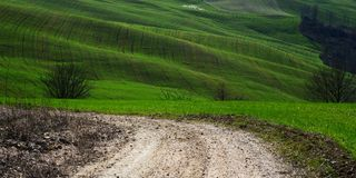 Country road. Curve leading to bright green hills royalty free stock photography
