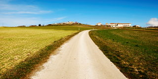 Country road. Narrow country road or lane across open fields leading to buildings royalty free stock photo