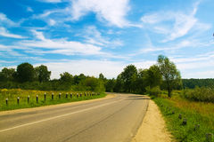 Country road. Blue skies, green grass, turning road and nobody around Royalty Free Stock Photos