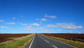 Country road. Red car travels on Yorkshire moors country road Stock Photography