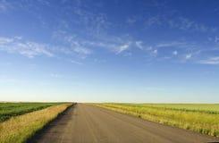 Country road. Gravel road running through farmland royalty free stock photos