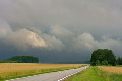 Country road across wheat fields and dark storm clouds Royalty Free Stock Images