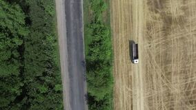 A country road along a field of golden grain under a bright blue sky. Aerial view stock footage