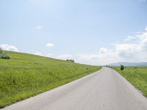 Country road. Along a green hill on a sunny day Royalty Free Stock Photography