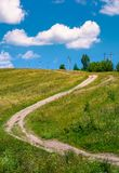 Country road along the hillside. Lovely countryside rural scenery in summer. beautiful blue summer sky with fluffy clouds Stock Photos