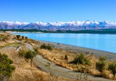 The country road along the Lake Tekapo and snowy mountains in autumn, Canterbury, South Island, New Zealand Stock Image