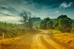 Country road in Australia. Country dirt road and farmland in the outer Leongatha district in Victoria, Australia stock images