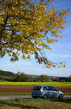 Country road in autumn. Car on a road leading through the German countryside royalty free stock image
