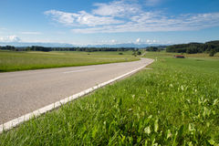 Country road in Bavaria with view to the alps Stock Photos